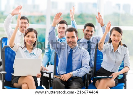 Business people at the conference raising hands to answer a question - stock photo