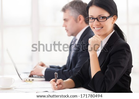 Business people at work. Cheerful young businesswoman sitting at the table and smiling at camera while mature man working on laptop on background - stock photo