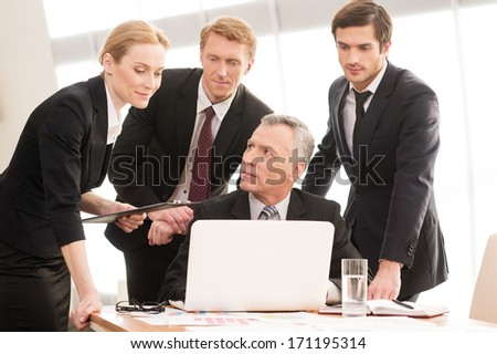 Business people at work. Four business people in formalwear discussing something and looking at laptop - stock photo