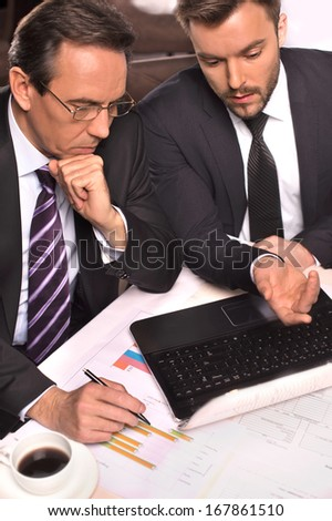 Business people at work. Top view of two business people in formalwear discussing something while one of them pointing computer monitor - stock photo