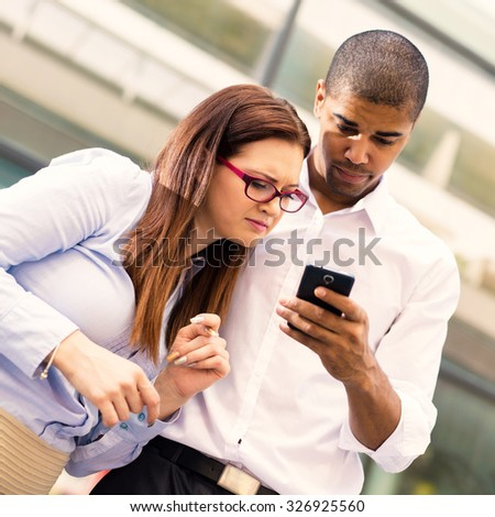 Business people. Black man holding smart phone and typing massage, while his colleague looking at mobile phone. Focus is on female. Shallow depth of field.