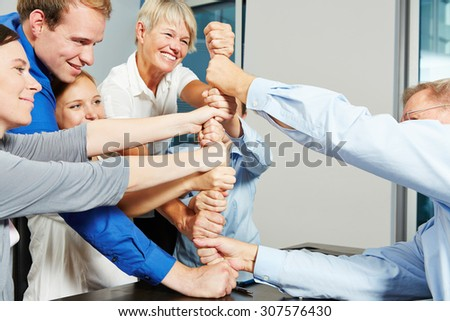 Business people building tower with their fists in a teamwork effort - stock photo