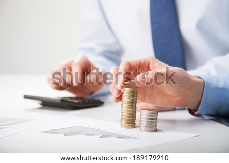 Business people calculating profit - closeup shot of hands counting coins - stock photo