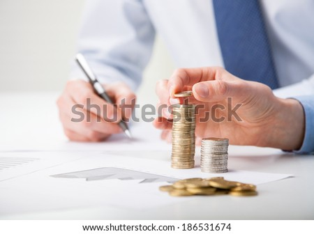 Business people calculating profit - closeup shot of hands counting coins and making notes on paper - stock photo
