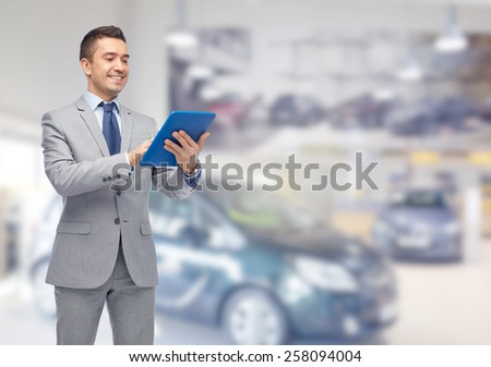 business, people, car sale and technology concept - happy smiling businessman in suit holding tablet pc computer over auto show or salon background - stock photo