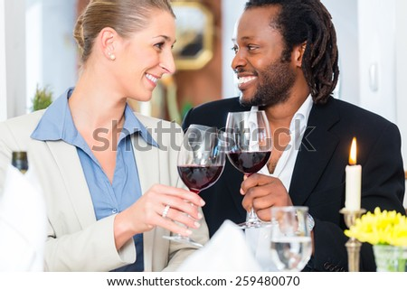 Business people, caucasian woman and african american man, toasting on deal with wine - stock photo