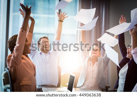 Business people celebrating by throwing papers in the air - stock photo