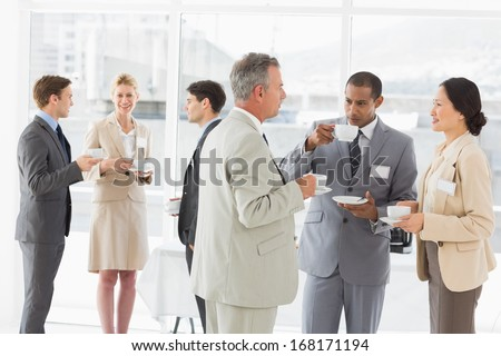 Business people chatting and drinking coffee at a conference in the office - stock photo