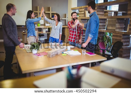 Business people cheering after meeting in creative office - stock photo