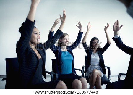 Business people cheering with arms in the air - stock photo