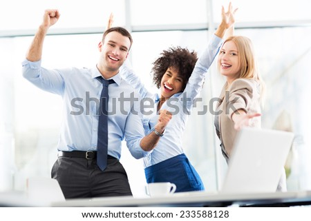 Business people cheering with arms raised - stock photo