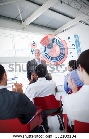 Business people clapping stakeholder standing in front of diagram interface showing statistics - stock photo