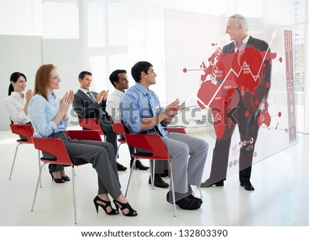 Business people clapping stakeholder standing in front of red map diagram interface in a meeting - stock photo