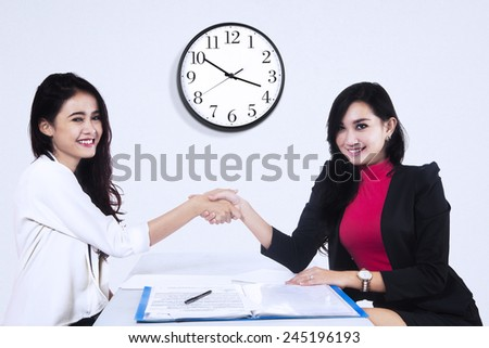 Business people closing a business deal by handshaking with white clock on the wall