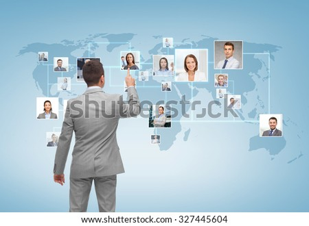 business, people, communication and technology concept - businessman pointing finger to contact icons on world map over blue background from back - stock photo