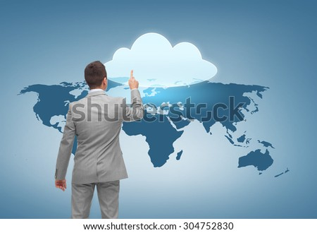 business, people, computing and technology concept - businessman pointing finger to cloud icon over blue background with world map from back - stock photo