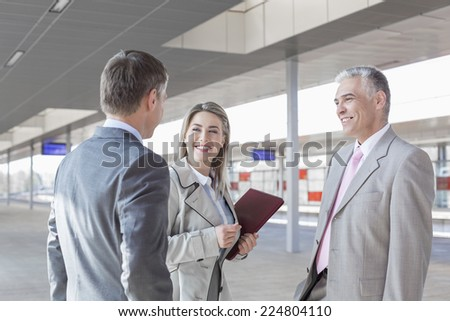 Business people conversing on train platform - stock photo