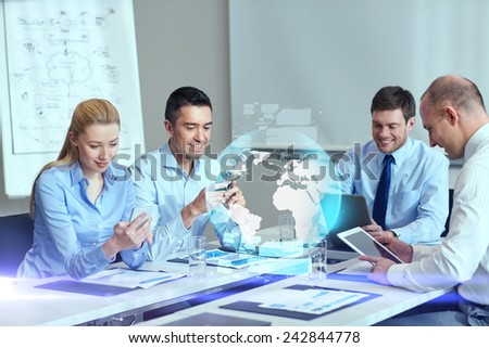 business, people, cooperation and technology concept - smiling business team with gadgets and globe hologram meeting in office - stock photo