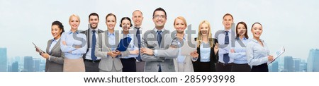 business, people, corporate, teamwork and office concept - group of happy businesspeople over city background - stock photo
