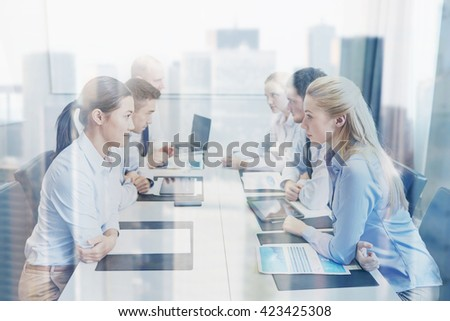 business, people, crisis and confrontation concept - smiling business team sitting on opposite sides in office - stock photo