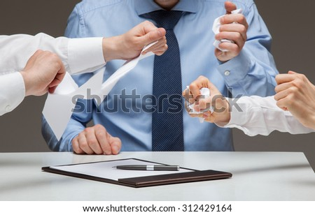 Business people cruelly tearing documents, gray background - stock photo