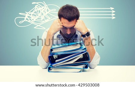 business, people, deadline, stress and paperwork concept - sad businessman with stack of folders over blue background and arrows - stock photo