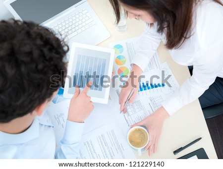 Business people developing a business project and analyzing information on a modern digital computer. View from above. - stock photo