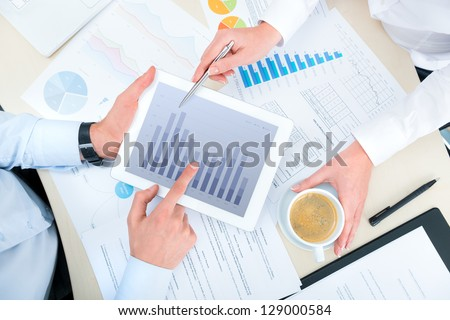 Business people discussing and analyzing market data information on a modern digital tablet computer. Top view photoshoot. - stock photo
