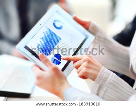 Business people discussing and analyzing market data information on a modern digital tablet compute - stock photo