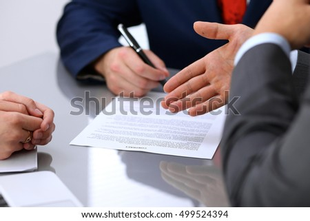 Business people discussing contract. Close up of male hand pointing to the paper