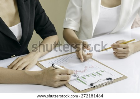 business people discussing financial graphic in a binder