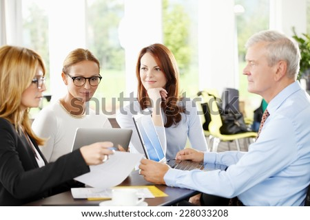 Business people discussing financial plans and working on laptop and tablet. Teamwork.  - stock photo