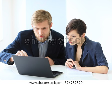 Business people discussing ideas at meeting using laptop in the office