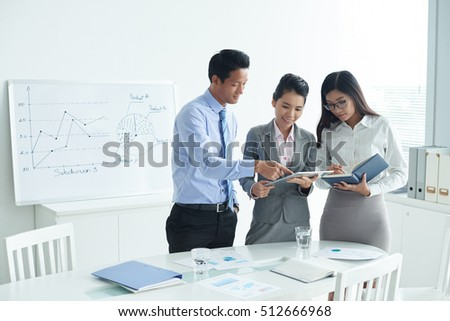 Business people discussing report on tablet computer