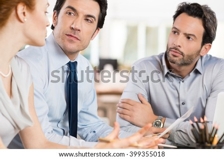 Business people discussing together their strategy at office. Businesswoman talking about the future of corporate with others businessmen. Business meeting in office.
