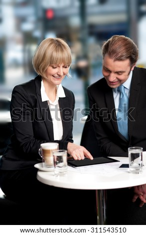 Business people discussing using tablet PC at cafe - stock photo