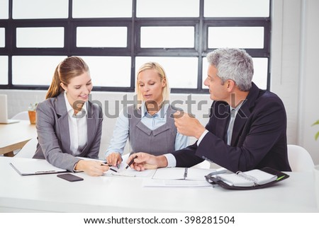 Business people discussing with client over documents at desk in office - stock photo