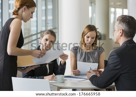 Business people doing paperwork in office cafeteria - stock photo