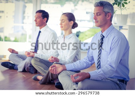 Business people doing yoga on floor in office - stock photo