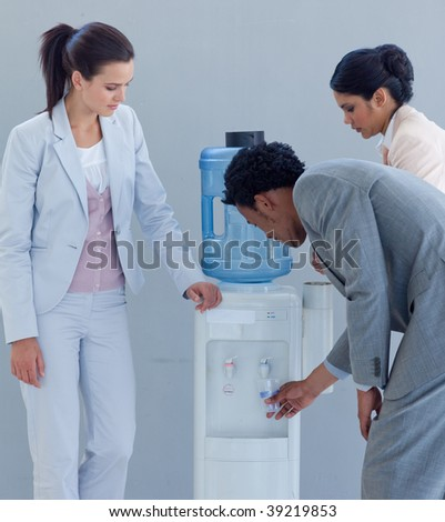 Business people drinking from a water cooler in office - stock photo