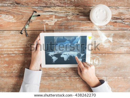 business, people, economics, statistics and technology concept - close up of hands pointing finger to tablet pc computer screen with virtual graph projection coffee cup and eyeglasses on table - stock photo
