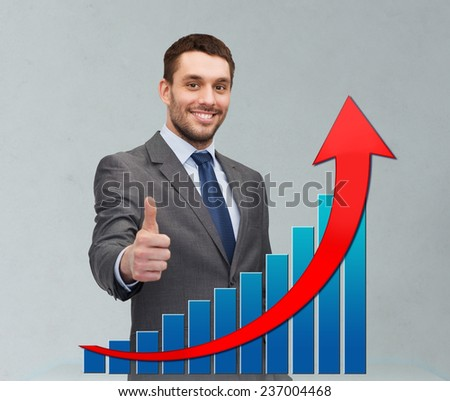 business, people, economics, success  and gesture concept - smiling young businessman showing thumbs up over gray background and growth chart