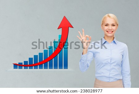 business, people, economics, success  and gesture concept - smiling young businesswoman showing ok sign over gray background and growth chart