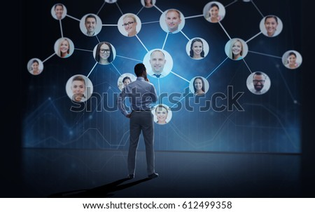business, people, employment, headhunting and network concept - businessman looking at virtual contact projection over dark background from back
