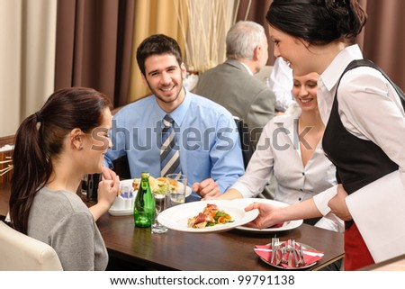 Business people enjoy lunch at the restaurant waitress serving woman - stock photo