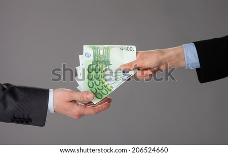 Business people exchanging euro banknotes on gray background - stock photo