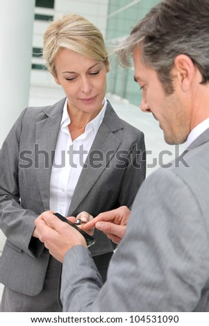 Business people exchanging phone numbers - stock photo