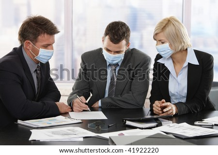Business people fearing h1n1 swine flu virus wearing protective face mask during meeting at office. - stock photo