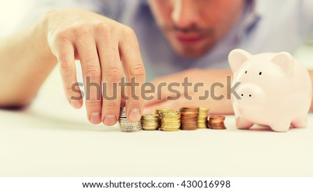 business, people, finances and money saving concept - close up of businessman with piggy bank and coins - stock photo