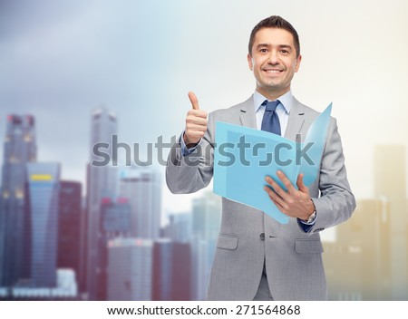 business, people, finances and paper work concept - happy smiling businessman in suit holding folder and showing thumbs up over city background - stock photo